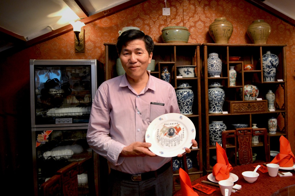 Alwyn holds up a plate that belonged to his grandfather.